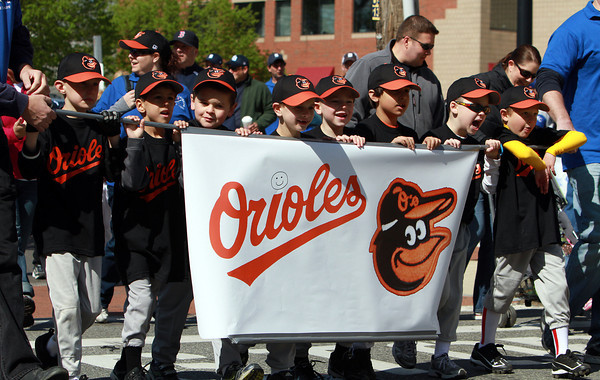 The Danvers American Orioles carry a banner through Danvers Square during the Little League Parade on Saturday. David Le/Staff Photo