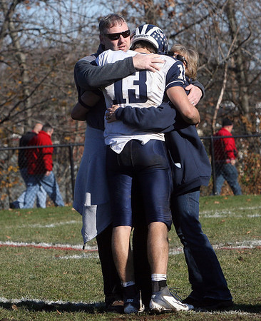Swampscott quarterback Mike Walsh gets a hug from his parents Karyn and Jim Walsh, following Swampscott's 21-7 loss to Marblehead on Thanksgiving morning.  David Le/Salem News