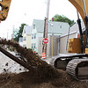 Salem: A construction worker on Bridge St. in Salem uses an excavator to snap an old trolley car rail in half. The rails were found underneath the concrete and run entirely up and down the busy street. Photo by David Le/Salem News