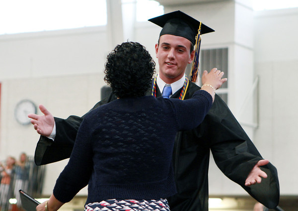 Beverly High School Senior Class President Jacob Levine gets a hug from Maria Decker, President of the Beverly School Committee, as he receives his diploma on Sunday afternoon. David Le/Staff Photo