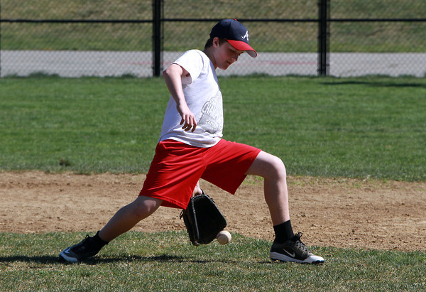Max Karass, 12, of the Marblehead Youth Baseball major league Braves fields a ground ball through his legs during a scrimmage against the Tigers. David Le/Staff Photo