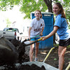 Masco sophomores Sarah Katz, left, and Olivia Binette, right, scoop dirt into a wheel barrow to be spread in the back yard of 23 Chase St. in Beverly, where Masco students are helping to restore the forclosed house as part of their Habitat for Humanity Club. David Le/Staff Photo