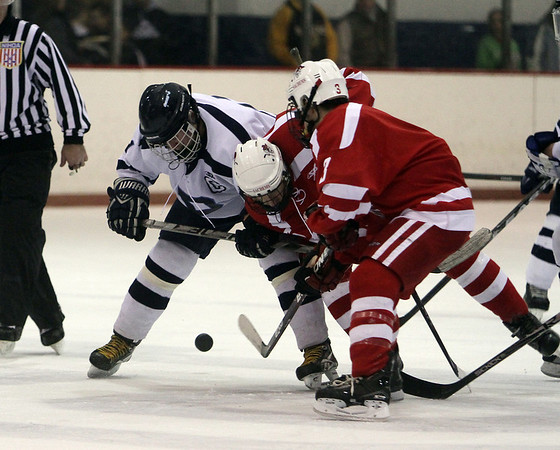Peabody Captain Tommy Burns, left, battles for a puck with two Saugus players on Wednesday night. <br /> David Le/Salem News