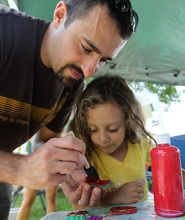 Julia Chirco, 5, of Beverly, gets help from her father Chris, while making a colorful flag during the Lobster Festival at Beverly Homecoming on Wednesday. David Le/Staff Photo