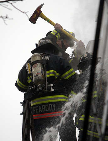 Peabody: Peabody firefighters work to break open the door to the third floor apartment on Friday afternoon as they tried to combat the 3-alarm blaze. David Le/Salem News
