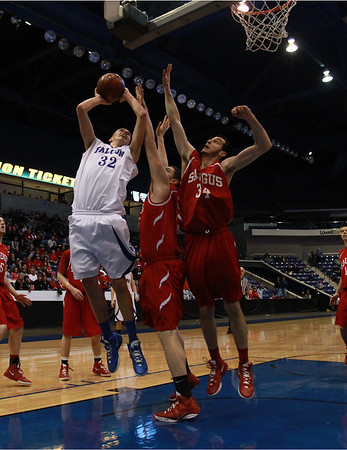 Danvers senior captain George Merry (32) left, goes up strong for a layup against two Saugus defenders during the D3 North Final at the Tsongas Center in Lowell on Saturday afternoon. David Le/Staff Photo