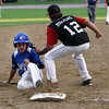 Peabody leadoff hitter Jake Gustin, left, slides safely into third base ahead of the tag from Marblehead third baseman DJ Migliore on Tuesday evening. David Le/Staff Photo