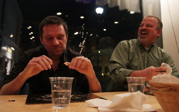 Darek Barcikowski, left, owner of Cafe Polonia, and Ward 5 Councilor Josh Turiel, right, square off in a packzi eating competition on Fat Tuesday. David Le/Staff Photo