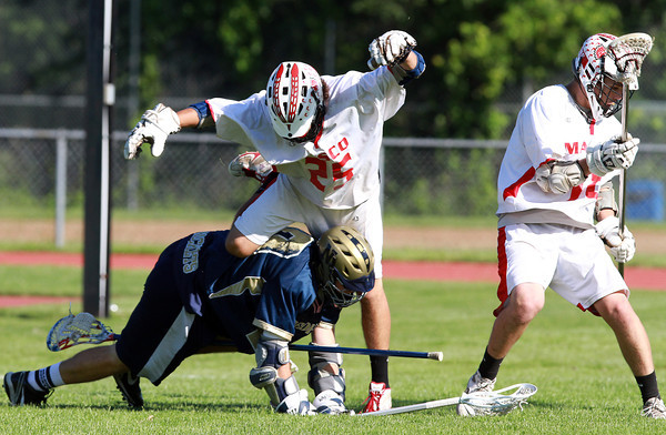 Masco's Cody Catarelli gets tangled up with a fallen Needham defender as they scramble for a loose ball. David Le/Staff Photo