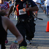 Beverly firefighter AJ Petronzio crosses the finish line of the Beverly Homecoming 5K Road Race on Thursday evening. Petronzio and a few other Beverly firemen ran the race wearing their fire gear. David Le/Staff Photo