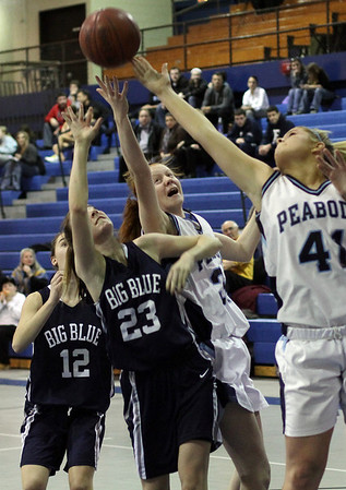 Swampscott's Niki Laskaris (23) battles for a rebound with Peabody's Caroly Scacchi (34) center, and Olivia Summit (41) right, on Friday night. David Le/Salem News