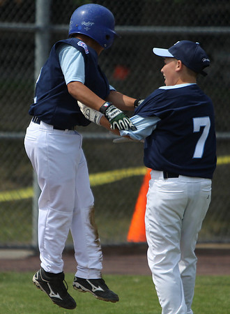 Danvers: Peabody National starting pitcher and leadoff hitter Christian Morales, left, is congratulated by Anthony Hartnett after scoring the first run of the game against Beverly West on Saturday morning in Danvers. Photo by David Le/Salem News