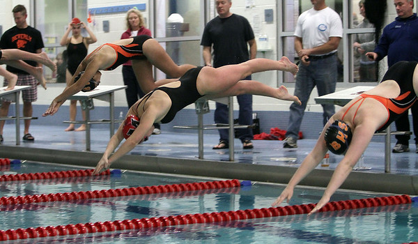 Beverly and Marblehead swimmers leap into the water at the start of the 200 freestyle race. David Le/Salem News
