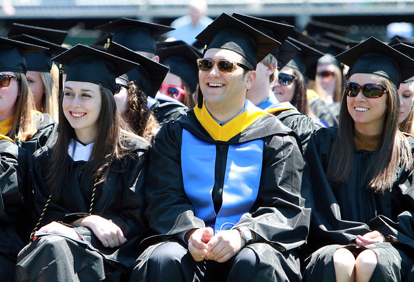 Endicott College seniors from left, Jackie Barthelmes, Michael Bedard, and Shannon Belfanti, laugh while listening to fellow classmate Greg Payne deliver a student speech on Saturday morning. David Le/Staff Photo