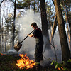 Danvers fireman Vic Romano uses a shovel to put out part of a brush fire in the woods behind Danvers High School late Friday afternoon. David Le/Staff Photo