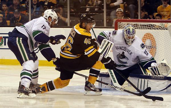 Marblehead native and Vancouver goalie Cory Schneider (35) tries to block a shot by Boston Bruins forward David Krejci as Vancouver's Ryan Kesler applies pressure. David Le/Salem News
