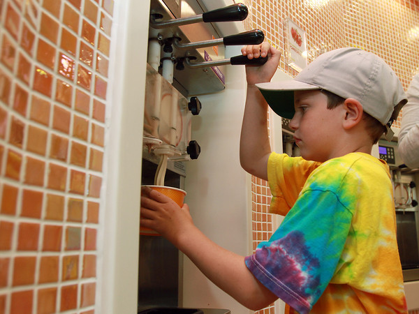 Carter Corbett, 6, of Marblehead concentrates while pouring himself some frozen yogurt at Orange Leaf, a brand new frozen yogurt shop at the corner of Lafayette and Derby Streets in downtown Salem. David Le/Staff Photo