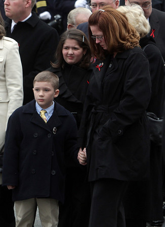 Peabody: Amy Rice, right, widow of firefighter Jim Rice, holds hands with her son Ryan, 7, left, and consols one of her daughters, Katelyn, 9, outside St. Vasilios Greek Orthodox Church on Friday morning. David Le/Salem News