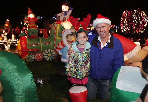 Ron Gagne, of Beverly, with his granddaughter Abby Mahler, 5, of Portsmouth in his backyard which he lavishly decorates with lawn ornaments and lights. This is the 4th year he has decorated his yard. David Le/Salem News
