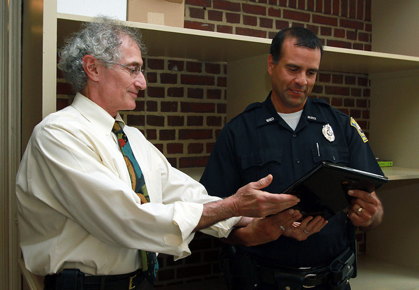 Bob Broudo, left, Headmaster of Landmark, and Chair of Citizens Advisory Council of the Beverly Police, presents the Police Officer of the Year Award to Marc Panjwani on Tuesday afternoon. David Le/Staff Photo