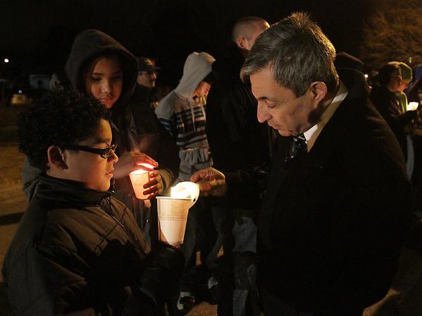 State Representative Ted Spiliotis gets his candle lit at a vigil for Stephanie Moulton, by Steven Nova, 10, and Pedro Hernandez, 12, of Peabody. David Le/Salem News