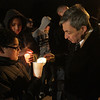 State Representative Ted Spiliotis gets his candle lit at a vigil for Stephanie Moulton, by Steven Nova, 10, and Pedro Hernandez, 12, of Peabody. David Le/Salem News