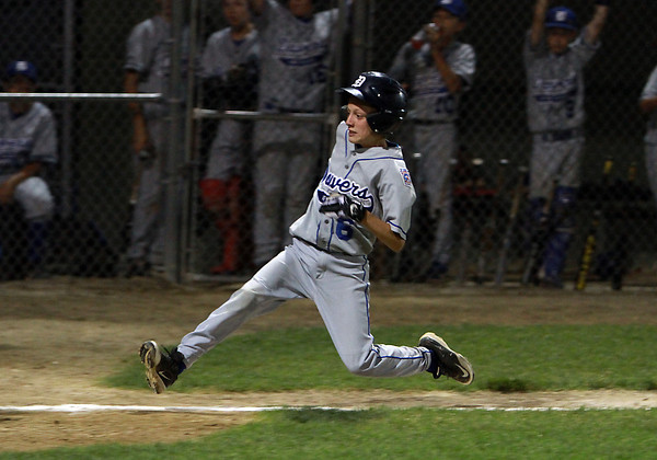Danvers American runner Nic DiScuillo is temporarily airborne as he slides into home plate with another Danvers run.