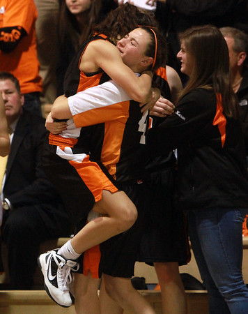 Ipswich freshman point guard Masey Zegarowski, left, jumps into the arms of teammate Natalie Soliozy as time winds down sending the Tigers to the D3 North Girls Basketball Final. David Le/Staff Photo