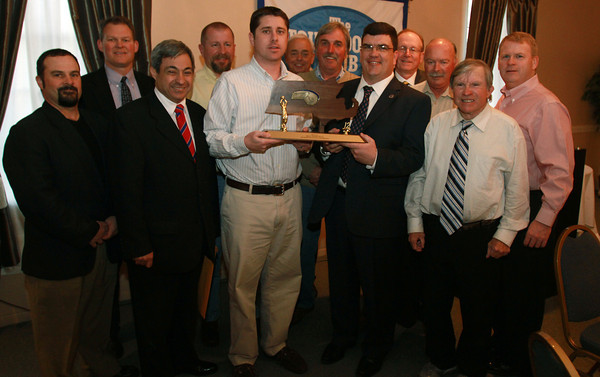 Danvers Head Basketball Coach John Walsh, center, holds the D3 State Championship Trophy with President of the Touchdown Club of Danvers, Rob Prentiss, and the Board Members of the Touchdown Club. David Le/Staff Photo