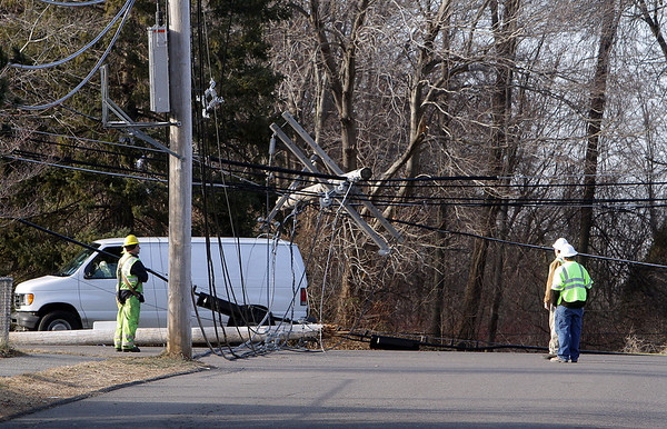 Peabody Municipal Light workers gaze up at part of a telephone pole suspended by the many wires attached to it after a truck ran into the pole and knocked it over. David Le/Salem News