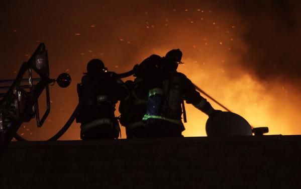 Firefighters work to put out a fire in an apartment complex from the roof on Wednesday night. David Le/Salem News