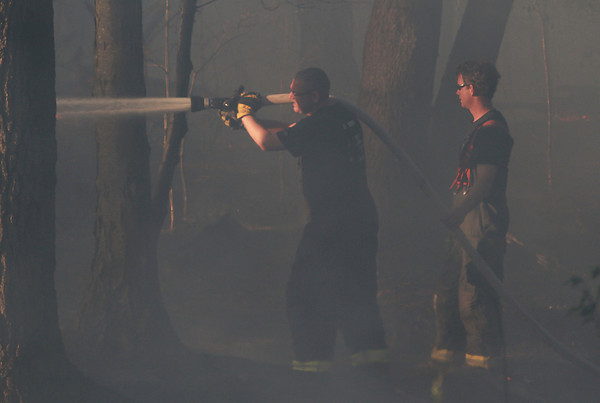 Danvers firefighters Ken Blankenship, left, and Vic Romano, right, fight a brush fire through heavy smoke on Friday afternoon. David Le/Staff Photo
