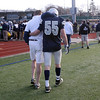 Hamilton-Wenham senior Taylor Drinkwater, right, walks off the field with the support of his brother and Generals assistant coach Mike Drinkwater after Hamilton-Wenham lost to Bourne High School 16-14 in the EMass D III A Superbowl at Manning Field in Lynn on Saturday afternoon. David Le/Salem News