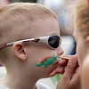 Samuel Magill, 4, of Salem, keeps his cool while getting a dinosaur painted on his face by Caitlyn O'Connell, of Salem, at the Ice Scream Bowl on Tuesday evening at Salem Common. David Le/Staff Photo