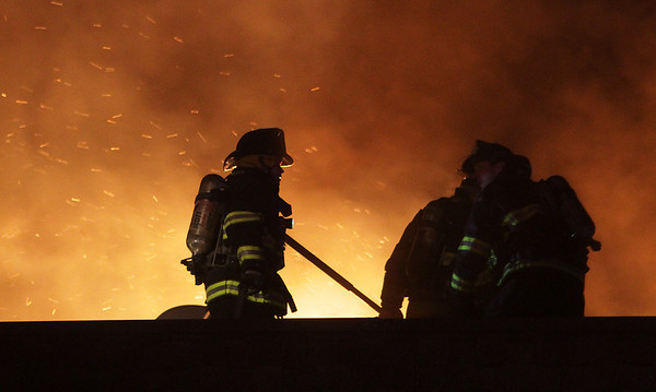 Firefighters work on the rooftop of a burning apartment complex on Folley Pond Road on Wednesday night. David Le/Salem News