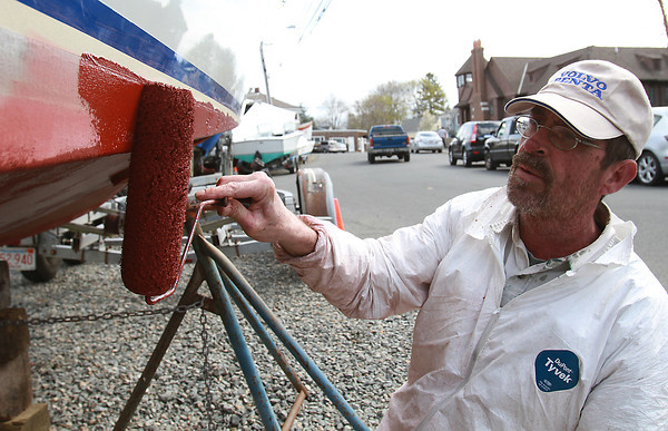 Rick Baker, a worker at CW Hood in Marblehead paints the bottom of a boat in the yard on Tuesday afternoon.David Le/Staff Photo