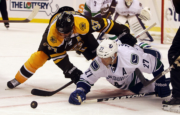 Bruins forward Patrice Bergeron and Canucks forward Manny Malholtra battle for the puck off a faceoff. David Le/Salem News