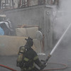 Peabody: Through thick billowing smoke a Peabody firefighter sprays water on the blaze at 5 Hancock St. on Friday afternoon. David Le/Salem News