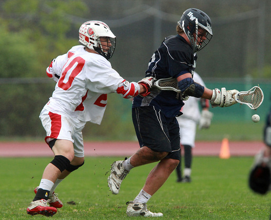 Hamilton-Wenham senior Elliott Burr, right, loses the ball while being stick checked by Masco's Dylan Mann, left, on Tuesday afternoon. David Le/Staff Photo