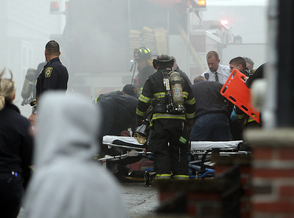 Peabody: Fire and rescue members work to resuscitate fireman Jim Rice at the scene of a 3-alarm fire on Friday afternoon. David Le/Salem News