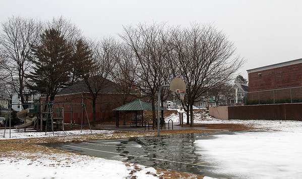 Melting snow and slush covered the basketball court and playground area at Splaine Park on Essex St. in Salem. David Le/Salem News