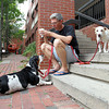 Jim Lemery, of Salem, sits on some steps near the Salem Farmer's Market and enjoys some ice cream with his dogs Willem, a Basset Hound, and Palomo, a Sato, on Thursday afternoon. David Le/Staff Photo