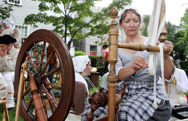 Penny Lacroix, of Westfield, spins a spool of thread from some wool during a re-enactment outside the Witch House Museum for the museum's annual Hearth and Field Day on Saturday morning. David Le/Staff Photo