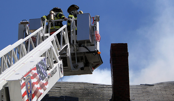 Above the still smoking roof of 20 Endicott St. two Peabody firefighters take a break after extinguishing the main blaze.  David Le/Staff Photo