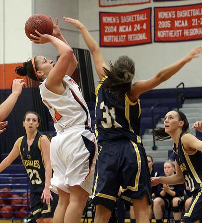 Salem State's Ginny Fleming (32) left, hoists up a shot as USM's Haley Jordan (31) provides pressure. David Le/Salem News