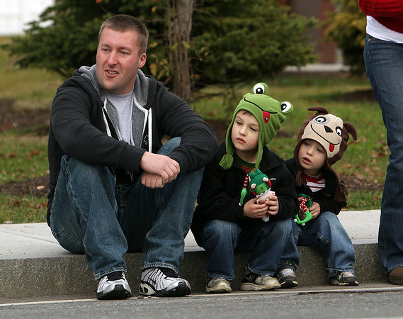 Rick Savickey, of Beverly, left, sits with his two sons Justin, 3, center, and Ethan, 2, while they watch the annual Beverly Holiday Parade on Sunday afternoon. David Le/Salem News
