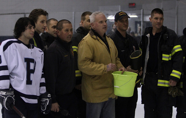 A few members of the Peabody Fire Department, and Peabody Hockey Captain Mike Chiappini, left, draw a number for the winning 50/50 raffle ticket, whos proceeds will go towards the Rice family in honor of Peabody Firefighter Jim Rice. David Le/Salem News
