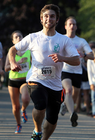 Andrew Ames, of Danvers, lets out a celebratory shout as he glances up at the clock and crosses the finish line of the 45th Annual Beverly Homecoming 5K Road Race. David Le/Staff Photo