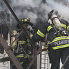 Peabody: Two Peabody firefighters work to combat the fire on Friday afternoon. David Le/Salem News