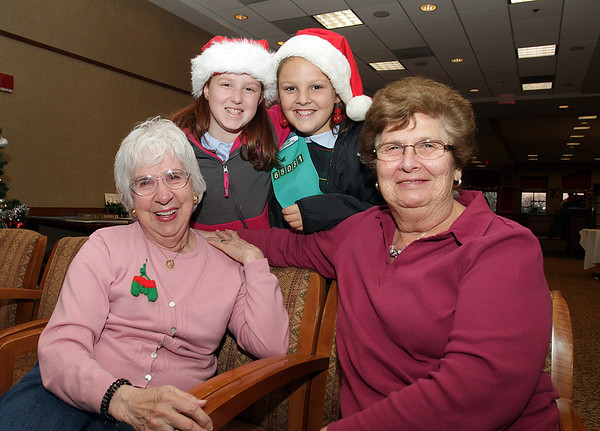 Peabody. Friends Theresa Usher, left, and Dot Chambers, right, sit with Chambers' granddaughter, Ally Pienta, back left, and Caitlin Vinagro, back right, after the girl scouts from St. John's performed Christmas songs at Brooksby Village on Tuesday afternoon.  David Le/Salem News